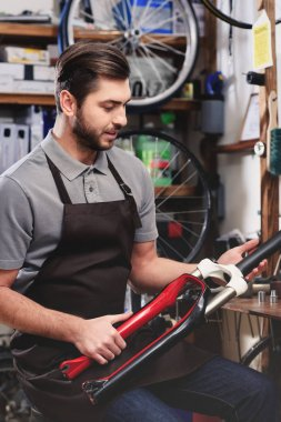 handsome young worker in apron repairing bicycle in workshop