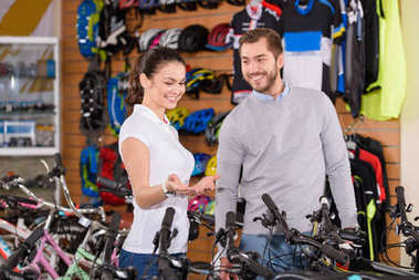 smiling young manager showing bicycles to customer in bike shop