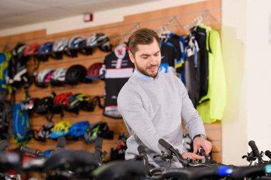 smiling young man choosing bikes at bicycle shop