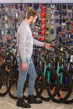 side view of young man looking at bikes in bicycle shop