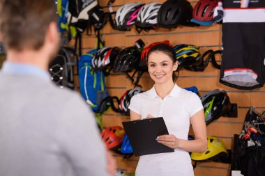 smiling young worker holding clipboard and looking at customer in bicycle shop