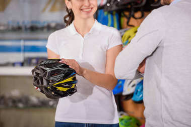 cropped shot of smiling seller showing bicycle helmet to customer in bike shop