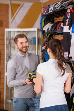 smiling male customer holding bicycle helmet and looking at seller in bike shop