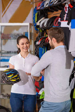 smiling female worker holding bicycle helmet and looking at buyer in bike shop