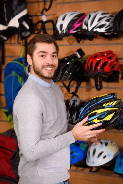handsome young man holding bicycle helmet and smiling at camera in bike shop