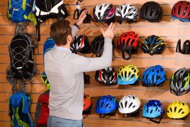 back view of young man choosing bicycle helmets in bike shop
