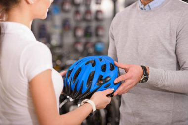 cropped shot of buyer and seller holding bicycle helmet in bike shop