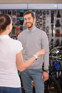 manager and smiling byer talking and looking at each other in bicycle shop