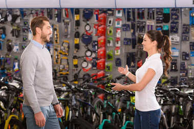side view of seller and customer talking in bicycle shop