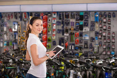 young woman holding digital tablet and smiling at camera while working in bicycle shop