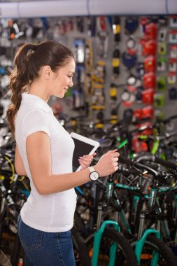 side view of smiling young woman holding digital tablet while working in bicycle shop