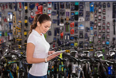 side view of smiling young woman using digital tablet while working in bike shop