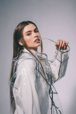 portrait of fashionable woman in trendy raincoat with eyeglasses looking at camera on grey background