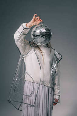 obscured view of stylish woman covering face with disco ball isolated on grey