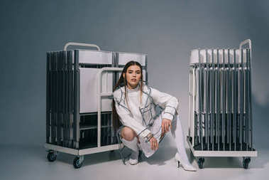 stylish woman in white clothing and raincoat with collapsible chairs behind looking at camera on grey background