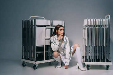 stylish woman in white clothing and raincoat with collapsible chairs behind looking away on grey background