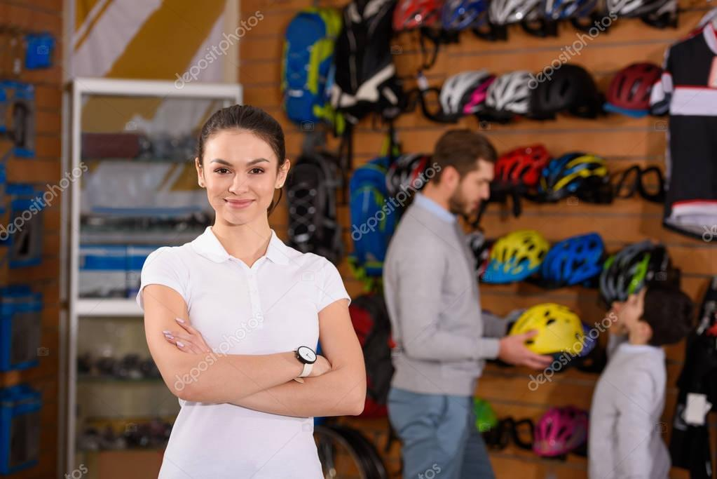 Young woman standing with crossed arms and smiling at camera while father and son choosing bicycle helmets behind in bike shop