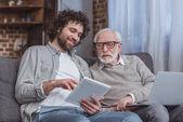 Fényképek felnőtt fia és a magas rangú apja segítségével a tábla- és laptop otthon