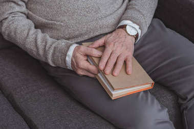 cropped image of grey hair man holding book at home