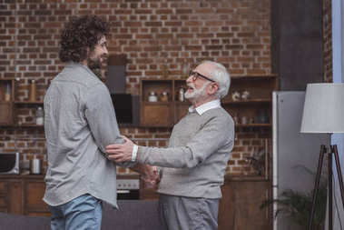 happy adult son and senior father shaking hands at home