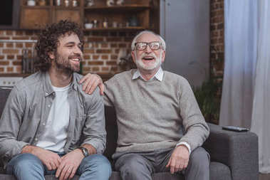 happy adult son and senior father laughing on sofa at home