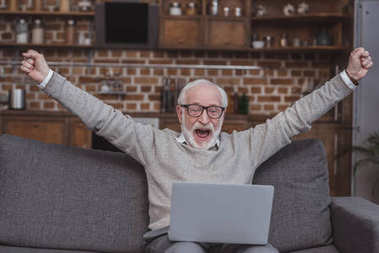 Happy grey hair man watching on laptop at home and celebrate win a bet with a gambling, soccer bet, sports gambling