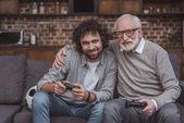 Fényképek vezető apja átölelve felnőtt fia közben videojáték otthon