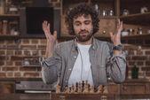 Fotografie gut aussehender Mann, gestikulieren und Blick auf Schach zu Hause