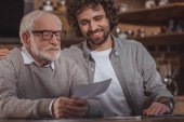 Fotografie smiling adult son hugging senior father and looking at photos at home