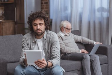adult son using tablet and senior father using laptop on sofa at home