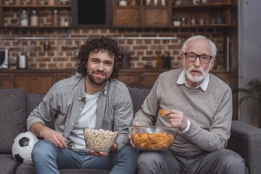 adult son and senior father watching football game with popcorn and chips at home