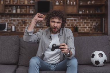 handsome man showing yes sign while playing video game at home