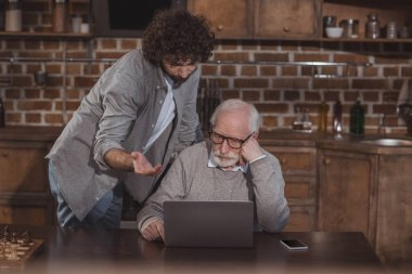 adult son and senior father looking at laptop at home