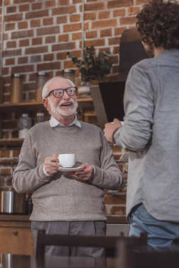 happy senior father and adult son talking with coffee in kitchen