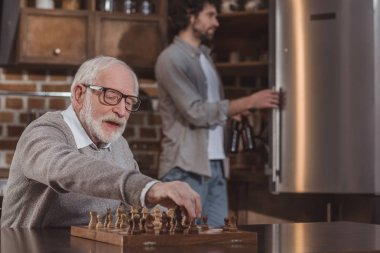 adult son looking in fridge and senior father playing chess at home
