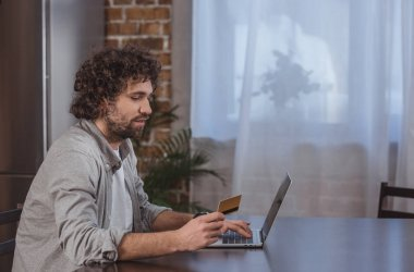 side view of handsome man shopping online at home