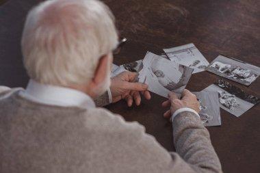 Rear view of grey hair man sitting at table and looking at photos at home stock vector