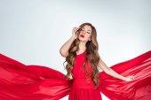 krásná smyslná žena pózuje v červené oblečení, izolované Grey