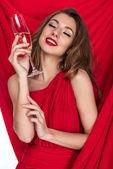 csukott szemmel tartja üveg pezsgőt piros ruhás érzéki lán
