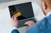 Fotografie Muž zaplatí nákup online s kreditní kartou a laptop
