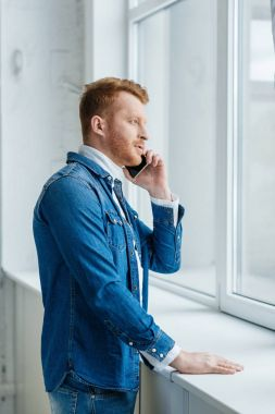 Young man talking on phone by window