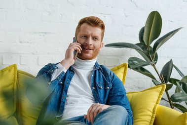 Businessman talking on phone while sitting on sofa