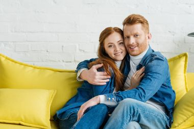 Embracing smiling couple sitting on sofa