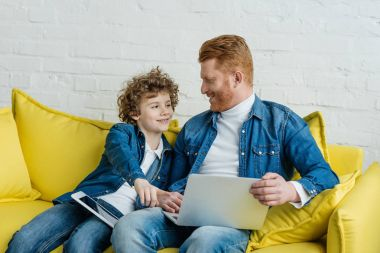 Father and son sitting on sofa with laptop and tablet