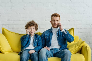 Father and son talking on smartphones looking at camera