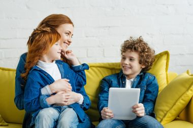 Hugging mother and daughter sitting on sofa with son holding tablet