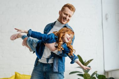 Father and little daughter playing pretending a plane
