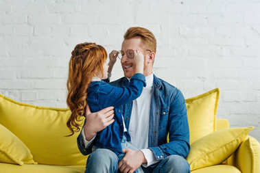 Daughter and father fooling with glasses while sitting on sofa