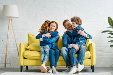 Happy children and parents hugging on sofa