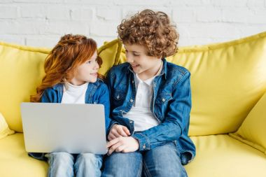 Cute kids using laptop while sitting on sofa